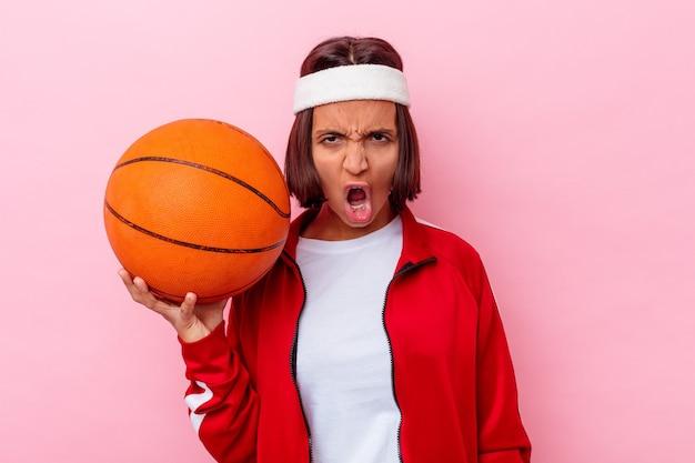 Młoda kobieta rasy mieszanej gry w koszykówkę na białym tle na różowym tle krzycząc bardzo zły i agresywny.