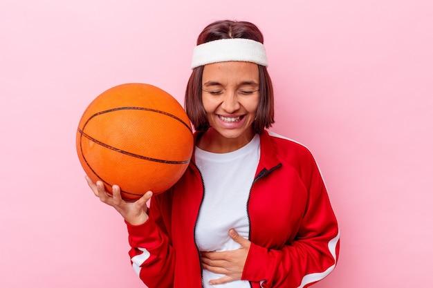 Młoda kobieta rasy mieszanej gry w koszykówkę na białym tle na różowym tle, śmiejąc się i zabawy.