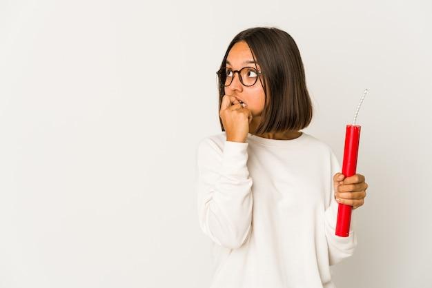 Młoda kobieta rasy mieszanej hispanic gospodarstwa dynamitu zrelaksowany myślenie o czymś, patrząc na przestrzeń kopii.