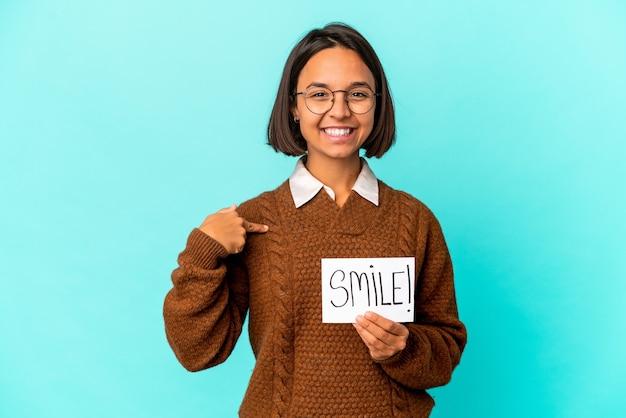 Młoda kobieta rasy mieszanej hispanic trzyma uśmiech uwaga osoba, wskazując ręką na przestrzeni kopii koszuli, dumny i pewny siebie