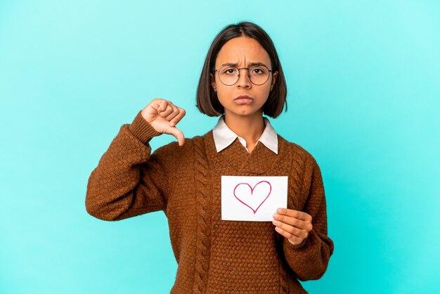 Młoda kobieta rasy mieszanej hispanic trzymając papier serca pokazujący gest niechęci, kciuki w dół. pojęcie sporu.