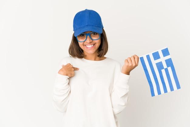 Młoda kobieta rasy mieszanej hiszpanin gospodarstwa flaga grecji osoba wskazująca ręką na miejsce na kopię koszuli, dumna i pewna siebie