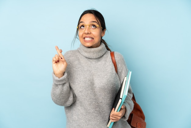 Młoda kobieta rasy mieszanej idzie do szkoły na białym tle na niebieską ścianą z palcami skrzyżowanymi i życząc jak najlepiej