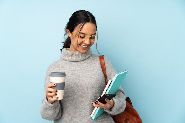 Młoda kobieta rasy mieszanej idzie do szkoły na białym tle na niebieskiej ścianie trzymając kawę na wynos i telefon komórkowy