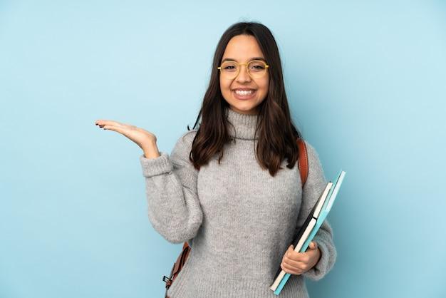Młoda kobieta rasy mieszanej idzie do szkoły na niebieską ścianą, trzymając puste miejsce na dłoni, aby wstawić reklamę