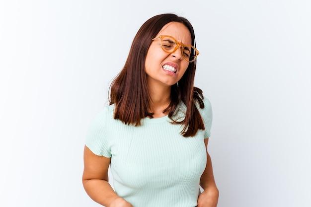 Młoda kobieta rasy mieszanej izolowane cierpi na ból pleców.