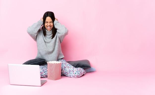 Młoda kobieta rasy mieszanej jedząca popcorn podczas oglądania filmu na laptopie sfrustrowana i zakrywająca uszy