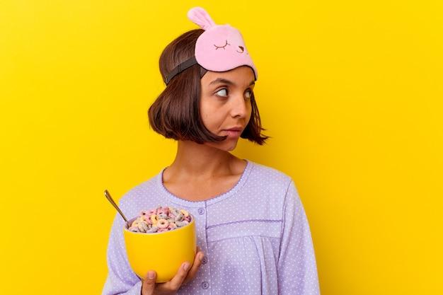 Młoda kobieta rasy mieszanej jedząca zboża w piżamie na żółtej ścianie wygląda na bok uśmiechnięta, wesoła i przyjemna.