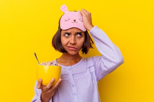 Młoda kobieta rasy mieszanej jedząca zboża w piżamie na żółtej ścianie, zszokowana, przypomniała sobie ważne spotkanie.