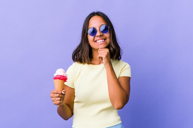 Młoda kobieta rasy mieszanej jedzenie lodów uśmiechnięty szczęśliwy i pewny siebie, dotykając brodą ręką.