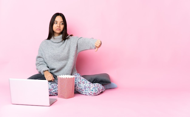 Młoda kobieta rasy mieszanej jedzenie popcornu podczas oglądania filmu na laptopie pokazując kciuk w dół z negatywnym wyrazem twarzy