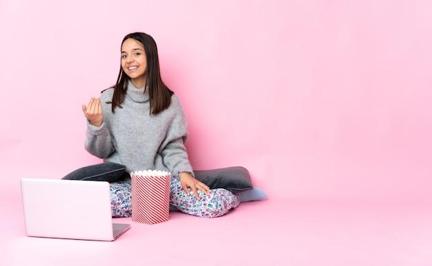 Młoda kobieta rasy mieszanej jedzenie popcornu podczas oglądania filmu na laptopie zapraszając do przyjścia z ręką. cieszę się, że przyszedłeś