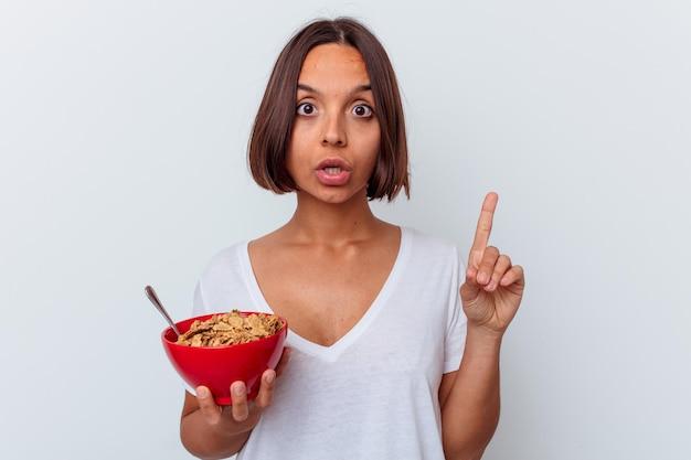Młoda kobieta rasy mieszanej jedzenie zbóż na białej ścianie, mając jakiś świetny pomysł, pojęcie kreatywności.