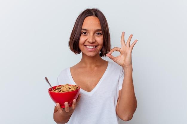 Młoda kobieta rasy mieszanej jedzenie zbóż na białej ścianie wesoły i pewny siebie, pokazując ok gest.