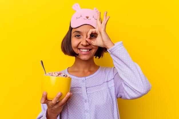 Młoda kobieta rasy mieszanej jedzenie zbóż ubrana w pijamę na białym tle na żółtej ścianie podekscytowany utrzymując ok gest na oko.