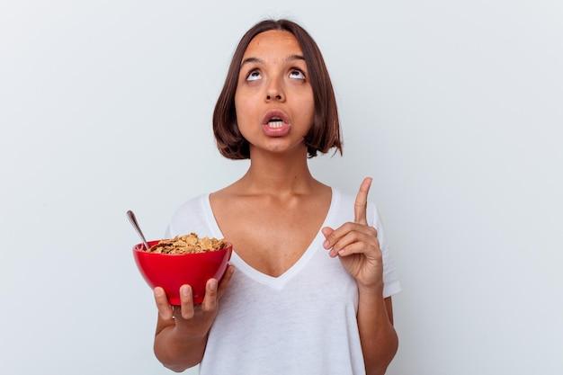 Młoda kobieta rasy mieszanej jeść zboża na białym tle na białej ścianie, wskazując do góry z otwartymi ustami.