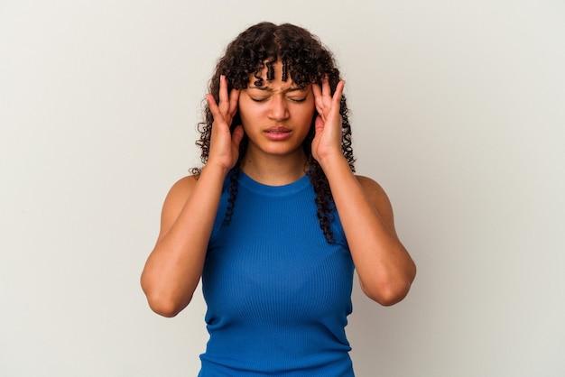 Młoda kobieta rasy mieszanej na białym tle dotykając świątyń i mając ból głowy.