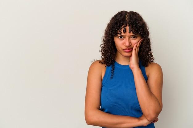 Młoda kobieta rasy mieszanej na białym tle, która czuje się smutna i zamyślona, patrząc na miejsce.