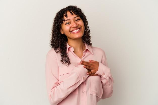 Młoda kobieta rasy mieszanej na białym tle ma przyjazny wyraz twarzy, przyciskając dłoń do klatki piersiowej. koncepcja miłości.