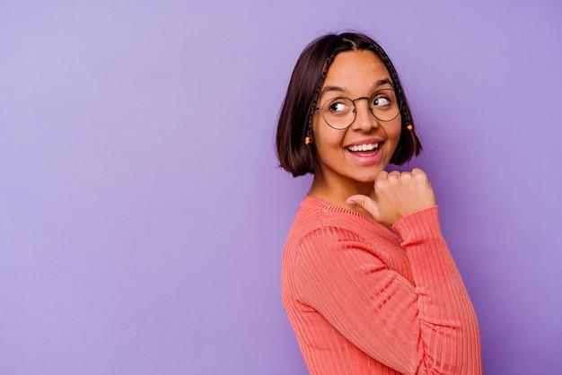 Młoda kobieta rasy mieszanej na białym tle na fioletowym tle wskazuje palcem kciuka, śmiejąc się i beztrosko.