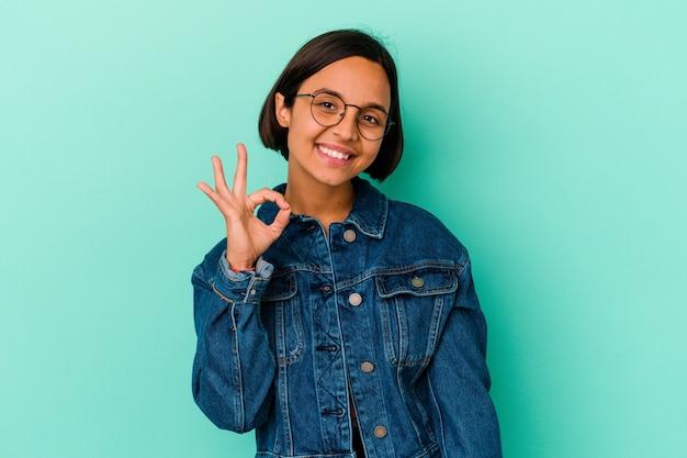 Młoda kobieta rasy mieszanej na białym tle na niebieskiej ścianie mruga okiem i trzyma w porządku gest ręką.