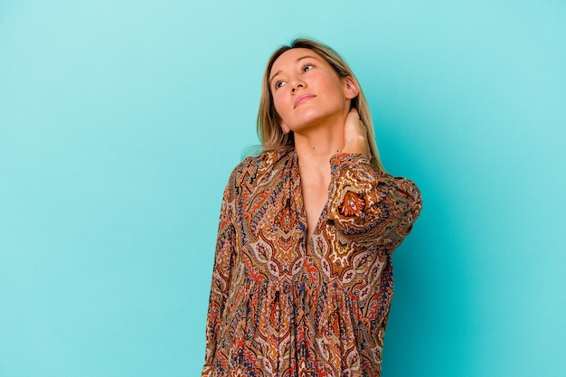 Młoda kobieta rasy mieszanej na białym tle na niebieskiej ścianie o bólu szyi z powodu stresu, masowania i dotykania jej ręką.