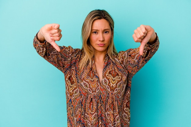 Młoda kobieta rasy mieszanej na białym tle na niebieskiej ścianie pokazując gest niechęci, kciuki w dół. pojęcie sporu.