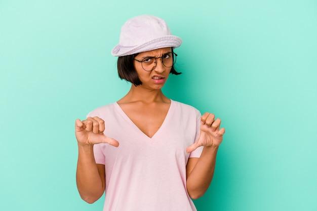 Młoda kobieta rasy mieszanej na białym tle na niebieskiej ścianie pokazując kciuk w dół i wyrażając niechęć.