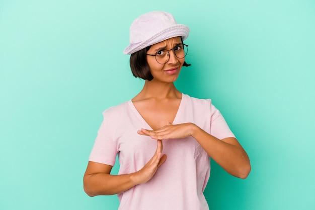 Młoda kobieta rasy mieszanej na białym tle na niebieskiej ścianie pokazujący gest limitu czasu.