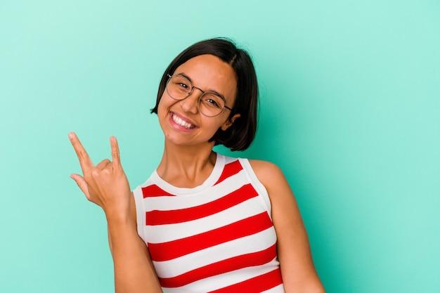 Młoda kobieta rasy mieszanej na białym tle na niebieskiej ścianie pokazuje gest rocka palcami