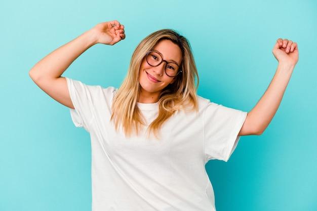 Młoda kobieta rasy mieszanej na białym tle na niebieskiej ścianie świętuje specjalny dzień, skacze i podnosi ramiona z energią.