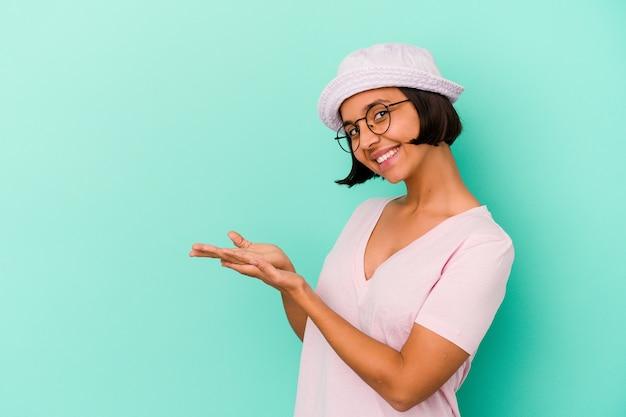Młoda kobieta rasy mieszanej na białym tle na niebieskiej ścianie trzyma miejsce na kopię na dłoni.