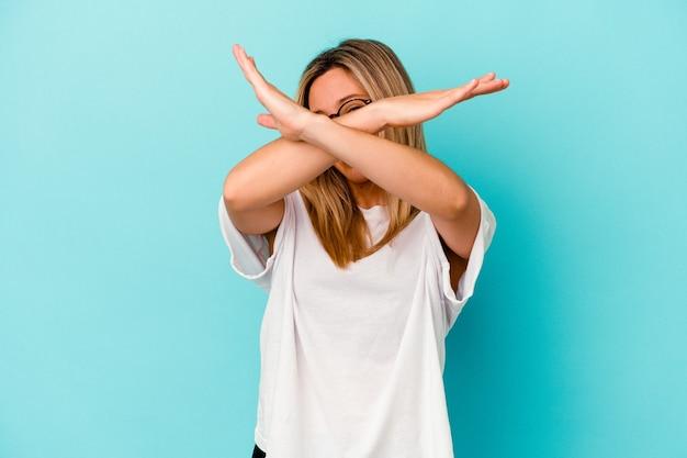 Młoda kobieta rasy mieszanej na białym tle na niebieskiej ścianie, trzymając dwa ramiona skrzyżowane, koncepcja odmowy.