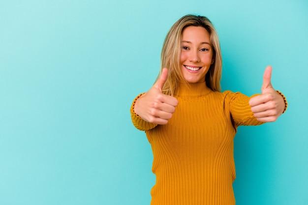 Młoda kobieta rasy mieszanej na białym tle na niebieskiej ścianie, uśmiechając się i podnosząc kciuk do góry
