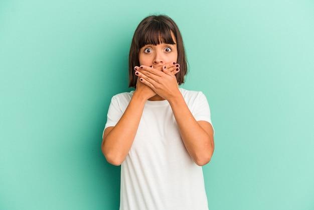 Młoda kobieta rasy mieszanej na białym tle na niebieskim obejmujące usta rękami patrząc zmartwiony.