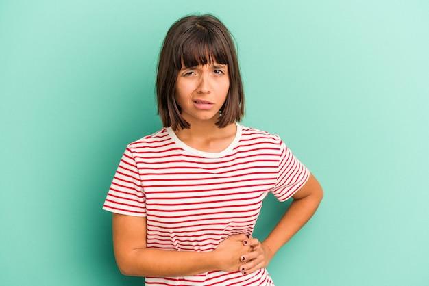 Młoda kobieta rasy mieszanej na białym tle na niebieskim tle obejmujące usta rękami patrząc zmartwiony.