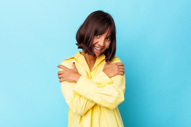 Młoda kobieta rasy mieszanej na białym tle na niebieskim tle przytula się, uśmiechając się beztrosko i szczęśliwie.