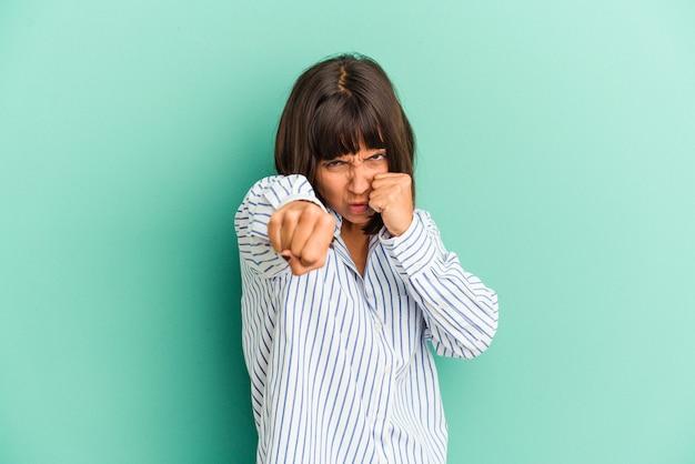 Młoda kobieta rasy mieszanej na białym tle na niebieskim tle, składając przysięgę, kładąc rękę na klatce piersiowej.