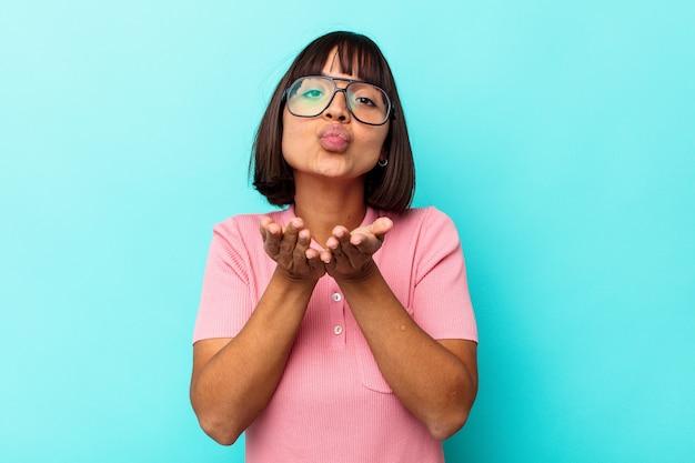 Młoda kobieta rasy mieszanej na białym tle na niebieskim tle składane usta i trzymając dłonie, aby wysłać pocałunek powietrza.