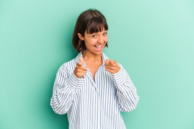 Młoda kobieta rasy mieszanej na białym tle na niebieskim tle śmieje się i zamyka oczy, czuje się zrelaksowana i szczęśliwa.