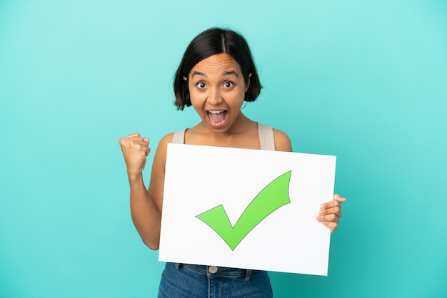 Młoda kobieta rasy mieszanej na białym tle na niebieskim tle trzyma tabliczkę z tekstem ikona znacznika wyboru i świętowania zwycięstwa