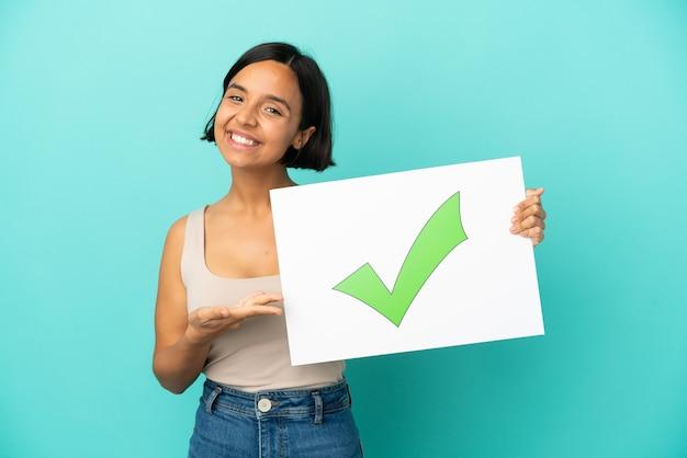 Młoda kobieta rasy mieszanej na białym tle na niebieskim tle trzyma tabliczkę z tekstem ikona znacznika wyboru i wskazując ją