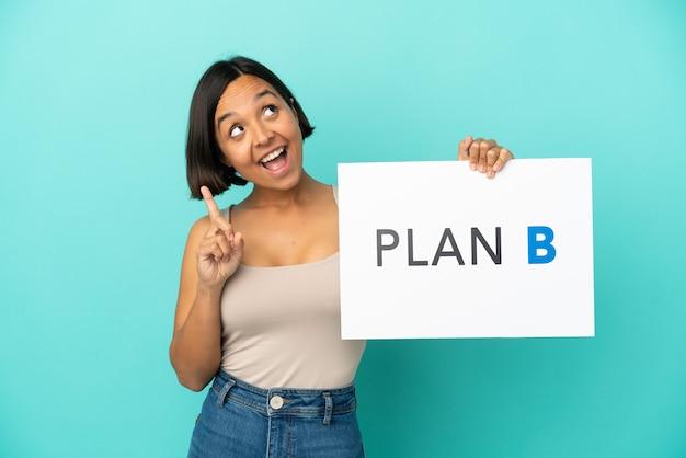 Młoda kobieta rasy mieszanej na białym tle na niebieskim tle trzymając tabliczkę z komunikatem plan b i myślenia