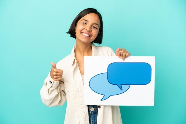 Młoda kobieta rasy mieszanej na białym tle na niebieskim tle trzymająca afisz z ikoną dymka z kciukiem do góry