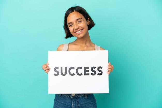 Młoda kobieta rasy mieszanej na białym tle na niebieskim tle trzymająca afisz z tekstem sukces ze szczęśliwym wyrazem