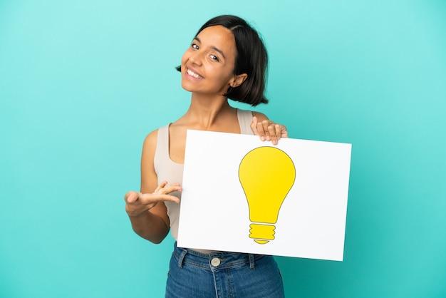 Młoda kobieta rasy mieszanej na białym tle na niebieskim tle trzymająca tabliczkę z ikoną żarówki i wskazującą ją