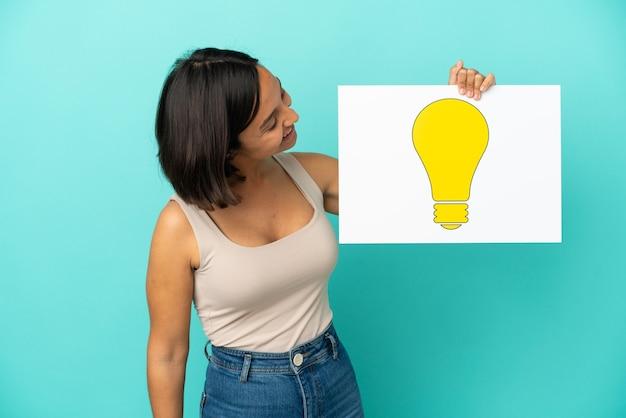 Młoda kobieta rasy mieszanej na białym tle na niebieskim tle trzymająca tabliczkę z ikoną żarówki