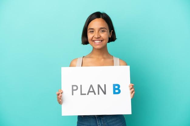 Młoda kobieta rasy mieszanej na białym tle na niebieskim tle trzymająca tabliczkę z komunikatem plan b ze szczęśliwym wyrazem twarzy
