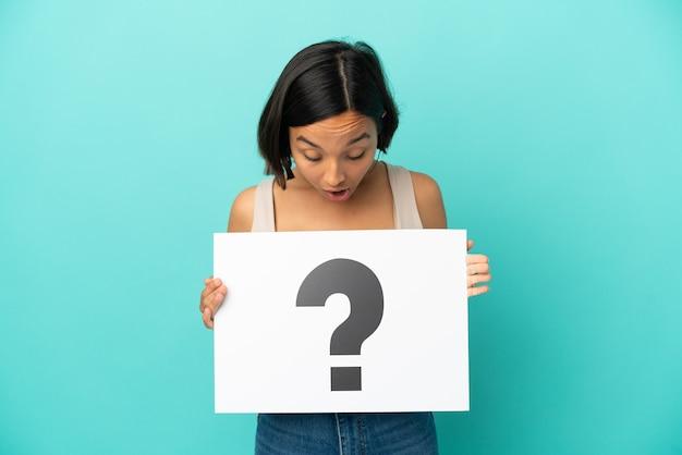 Młoda kobieta rasy mieszanej na białym tle na niebieskim tle trzymająca tabliczkę z symbolem znaku zapytania