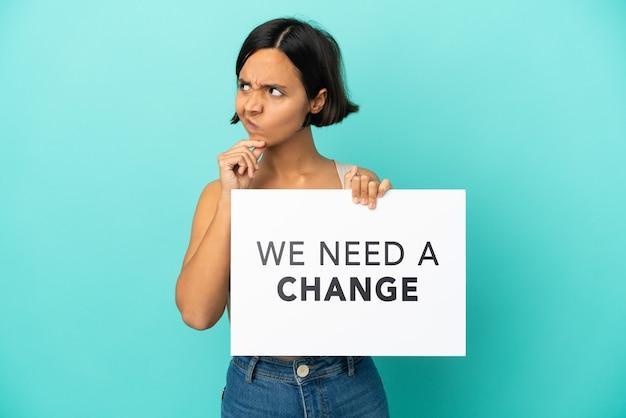 Młoda kobieta rasy mieszanej na białym tle na niebieskim tle trzymająca tabliczkę z tekstem potrzebujemy zmiany i myślenia